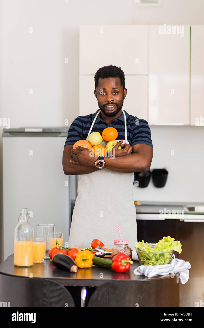 Attractive smiling bearded young dark skinned man wearing apron holding fresh ripe organic oranges, apples and grapefruit, making fruit smoothie, enjo Stock Photo
