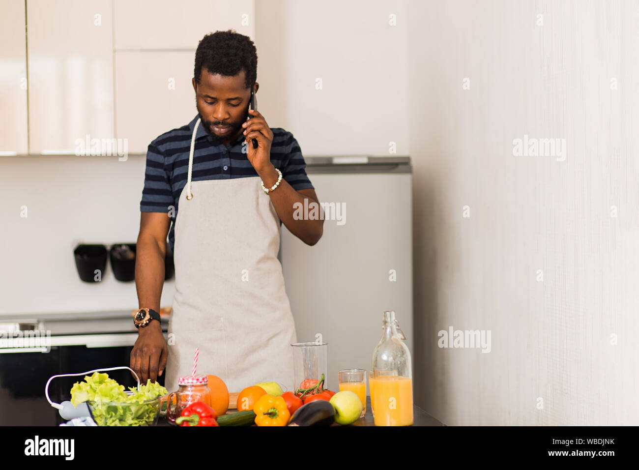 Portrait of serious young unshaven african man wearing apron standing in the white kitchen talking on mobile phone. Closeup shot. Cooking, communicati Stock Photo