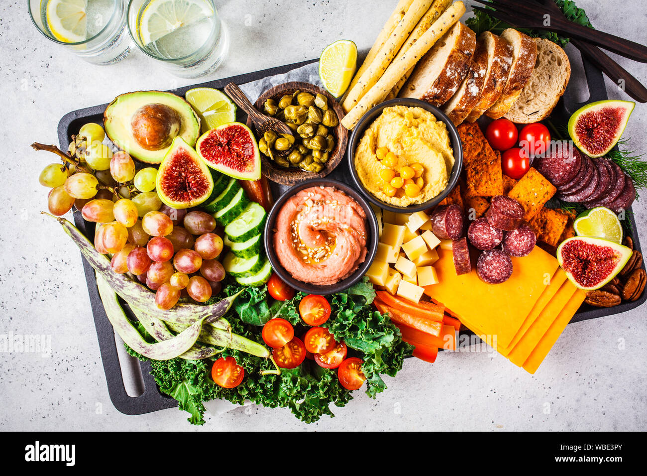 Meat And Cheese Appetizer Platter Sausage Cheese Hummus Vegetables Fruits And Bread On A Black Tray White Background Stock Photo Alamy