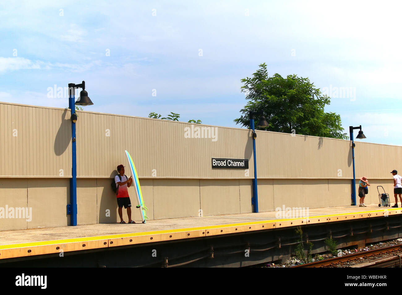 Lone surfer with a surfboard awaits subway train on the Broad Channel platform on a hot summer afternoon on August 18th, 2019 in Queens, New York, USA Stock Photo