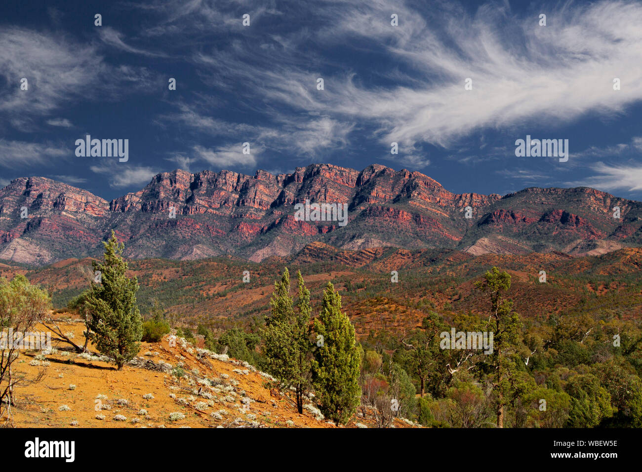 Stunning landscape in Flinders Ranges National Park with rugged red rocky ranges reaching up into blue sky streaked with clouds, South Australia Stock Photo