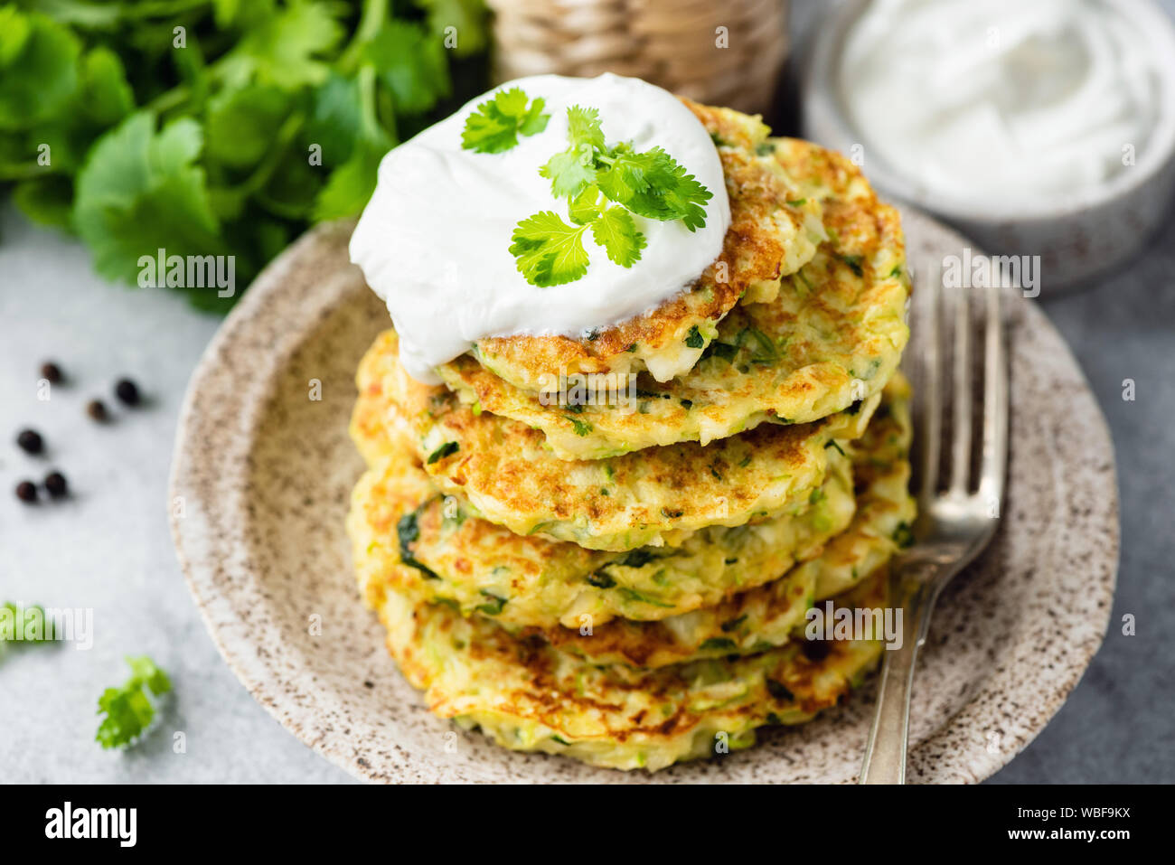 Zucchini fritters or pancakes stack with sour cream on top. Healthy vegetable patties Stock Photo