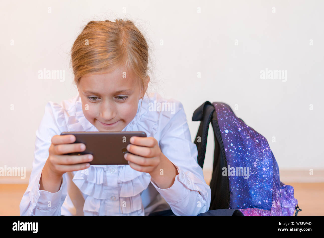 School girl plays on the smartphone. Kid play game, surfing online,  learning...etc. Mockup. vertical photo. Back to School Stock Photo - Alamy