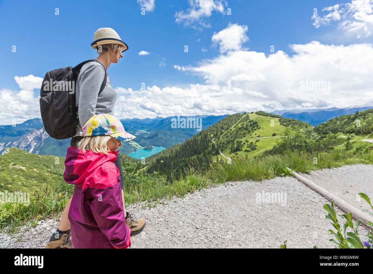 Side View Of Mother And Daughter Walking On Mountain Against Cloudy Sky Stock Photo