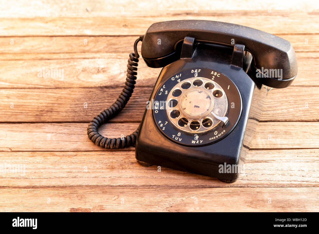 Retro rotary black telephone on wood table background. Old telephone with rotary dial. Stock Photo