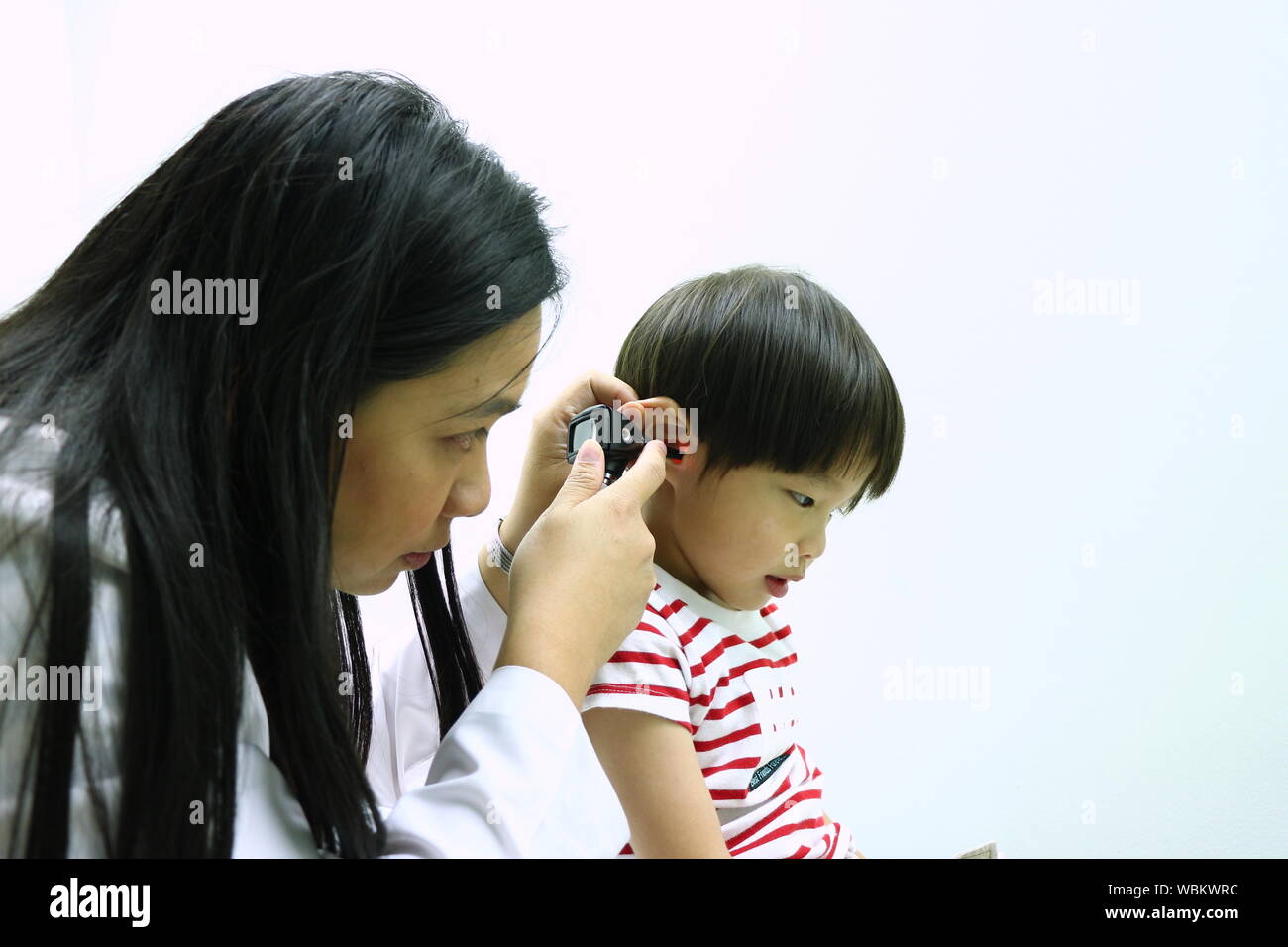 Female Doctor Checking Boy Ear With Otoscope Against White Background Stock Photo
