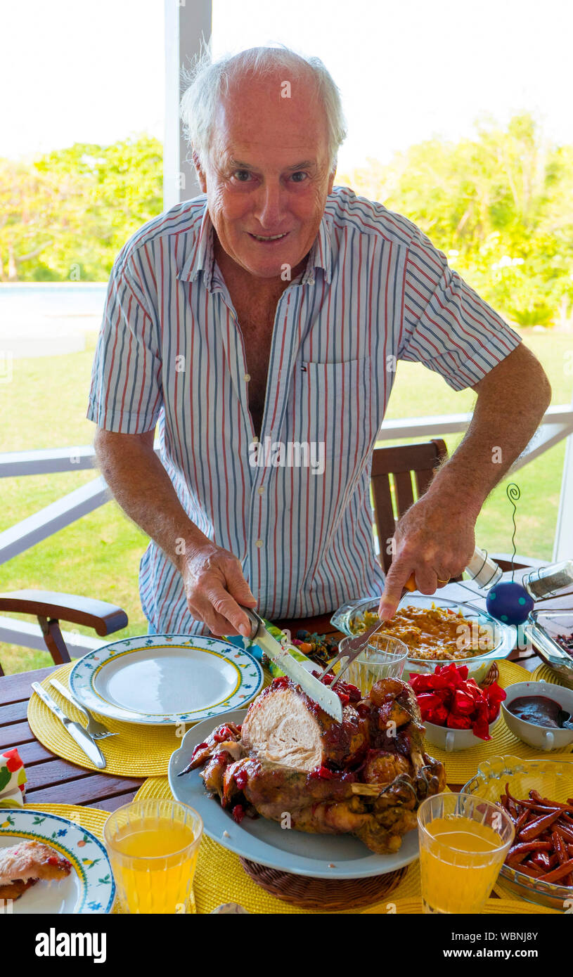 Man carving the Xmas turkey on the lunchtime table in the caribbean . Stock Photo