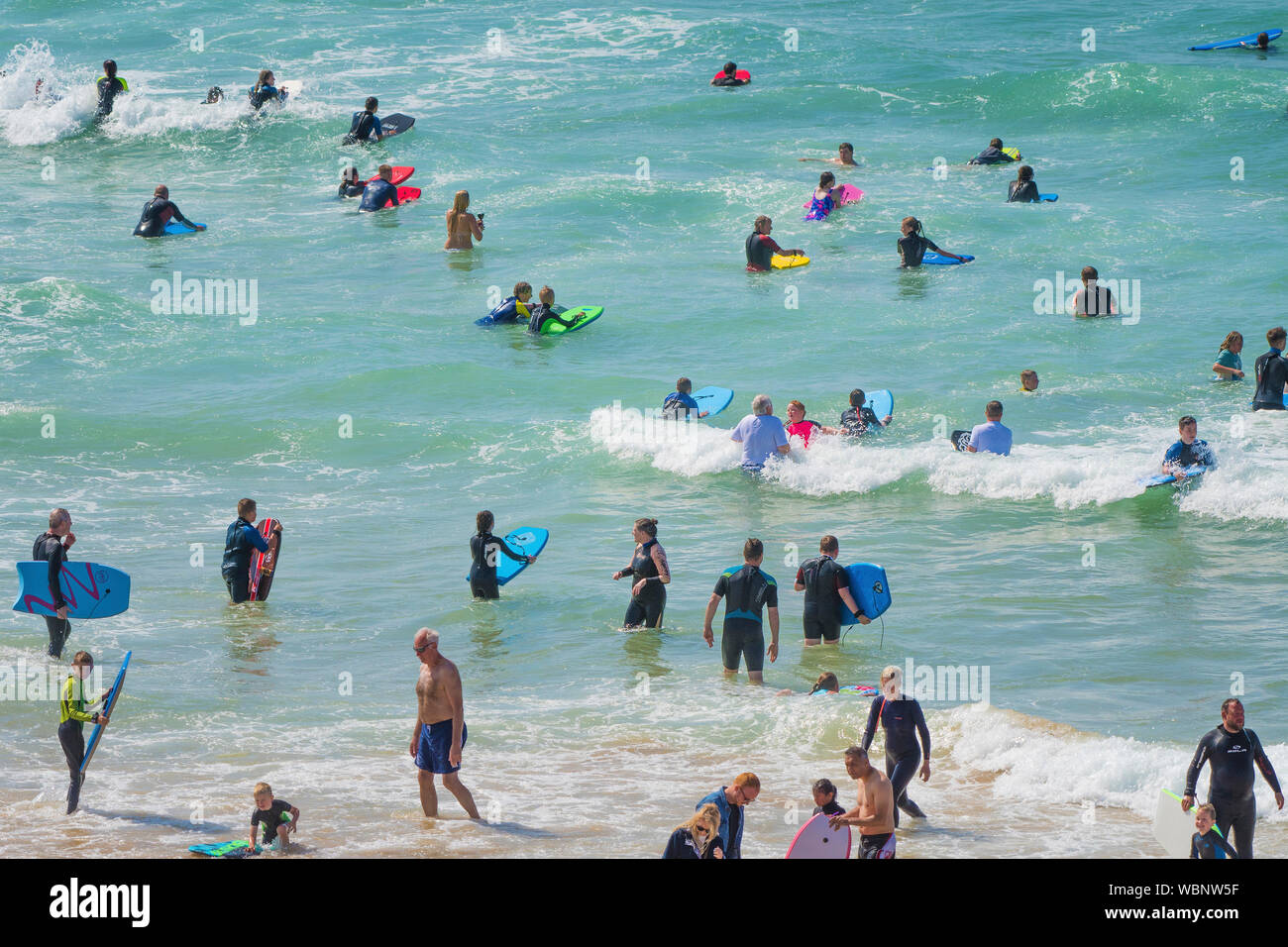 Holidaymakers on a staycation holiday enjoying themselves in the sea at Fistral in Newquay in Cornwall. Stock Photo