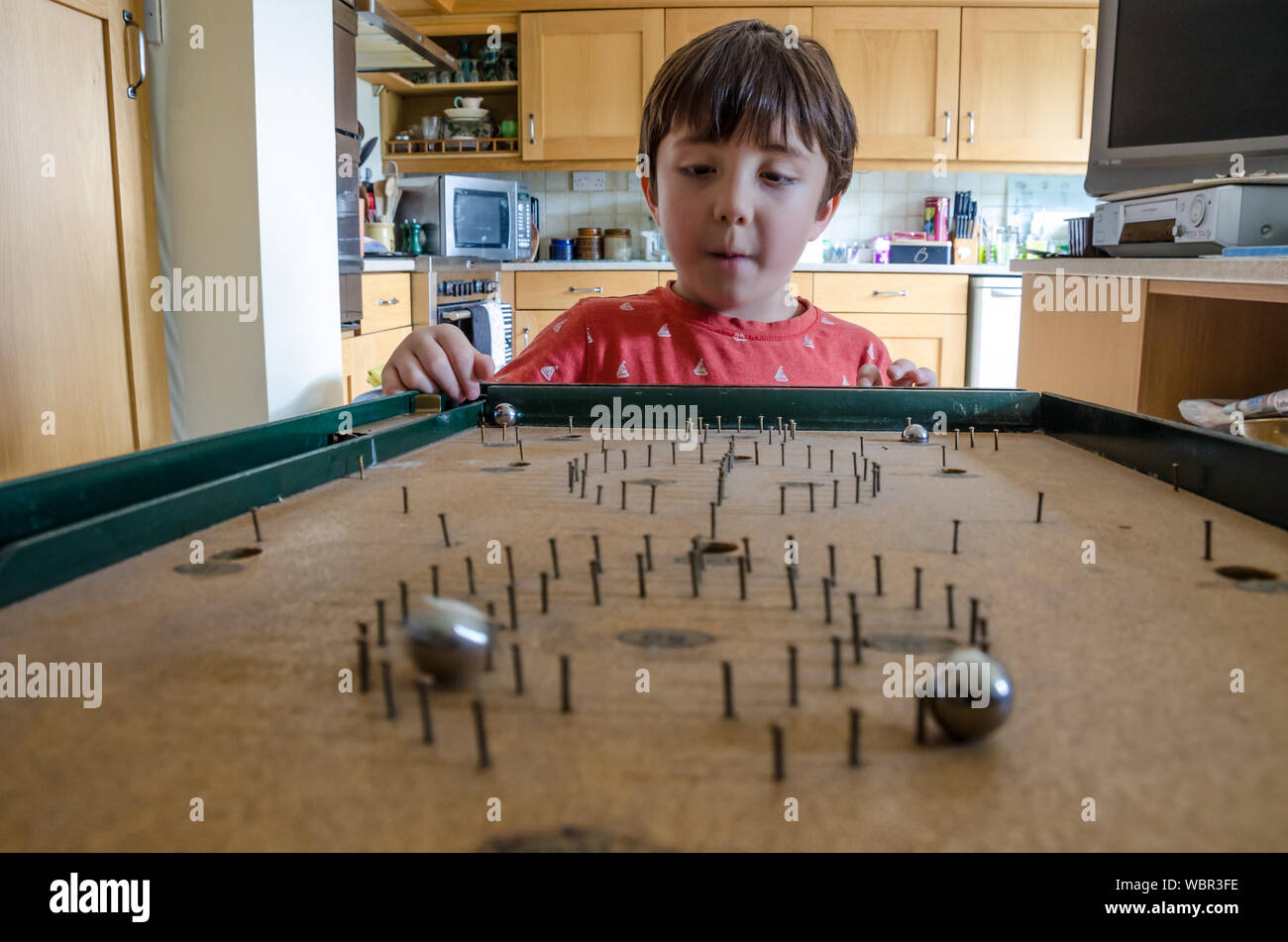 Cute Boy Playing Bagatelle At Home Stock Photo