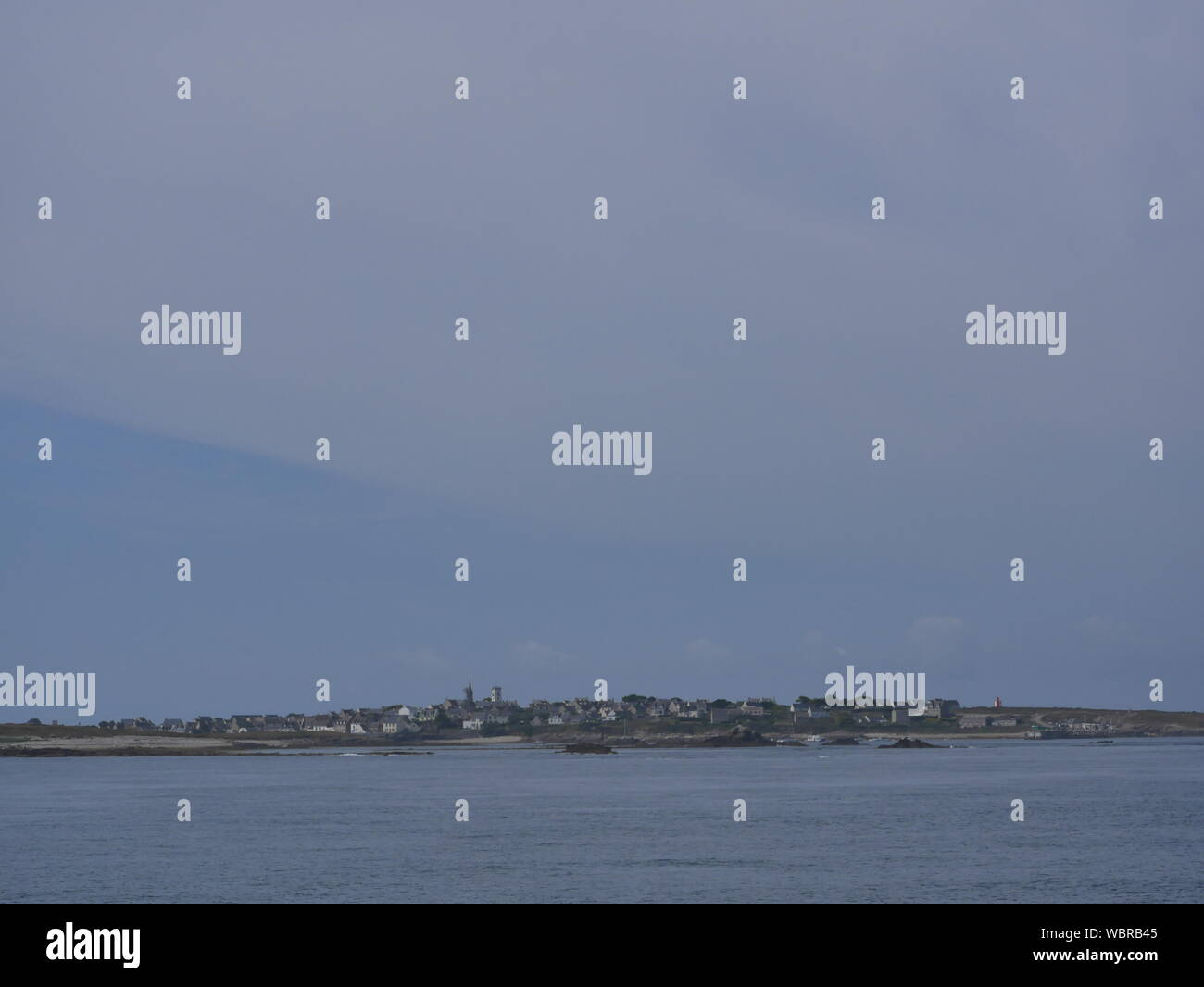 l'île de molène et son merveilleux port et ses bateaux multicolors et ses quais en granit et un banc bleu et blanc et l'île prise depuis le large Stock Photo
