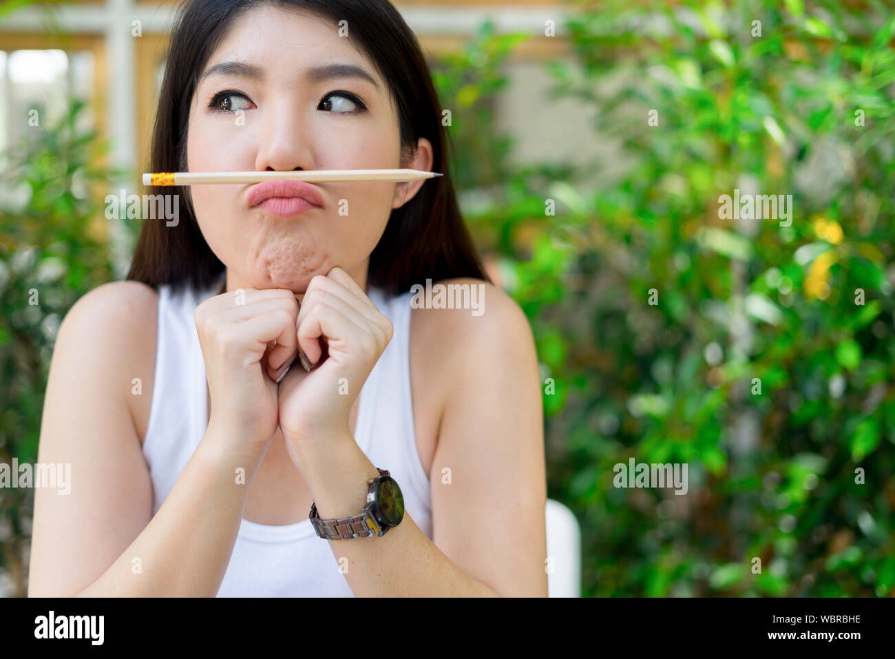 Close-up Of Playful Young Woman Balancing Pencil On Lips Stock Photo