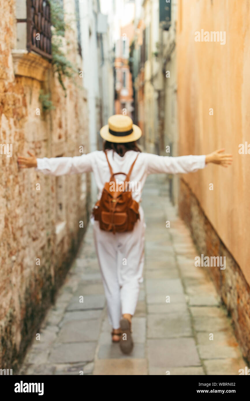 woman in white clothes in straw hat and brown leather backpack walking by city street Stock Photo