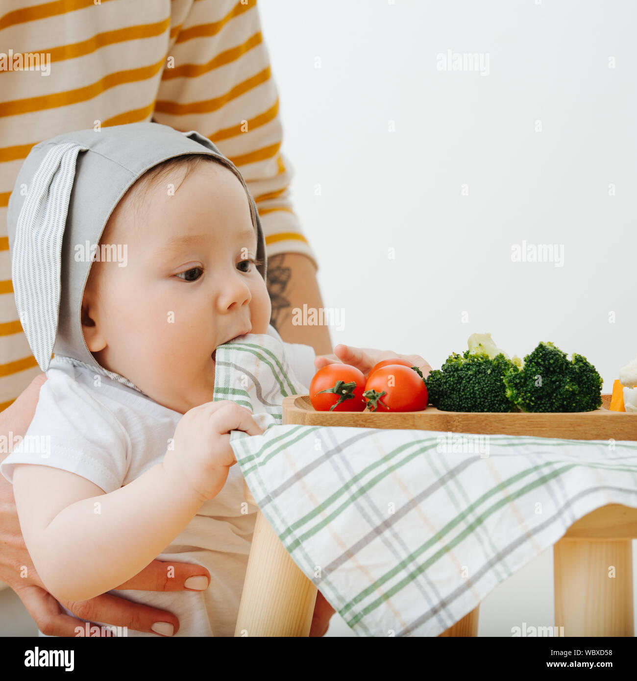 Active restless infant child is presented food Stock Photo