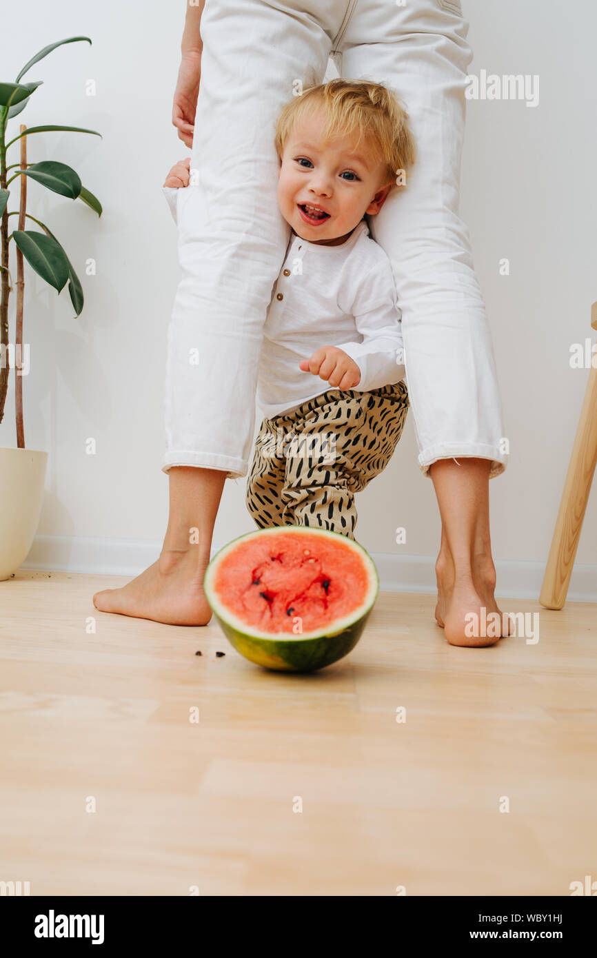 Little toddler boy, mother's legs arch and watermelon half slice Stock Photo