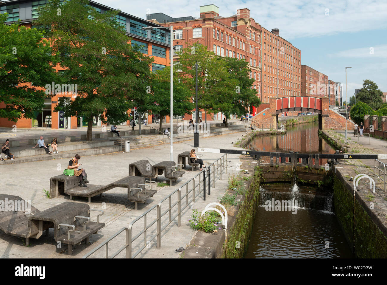 People enjoy the sunshine by the Rochdale Canal in Ancoats, Manchester, UK. Stock Photo