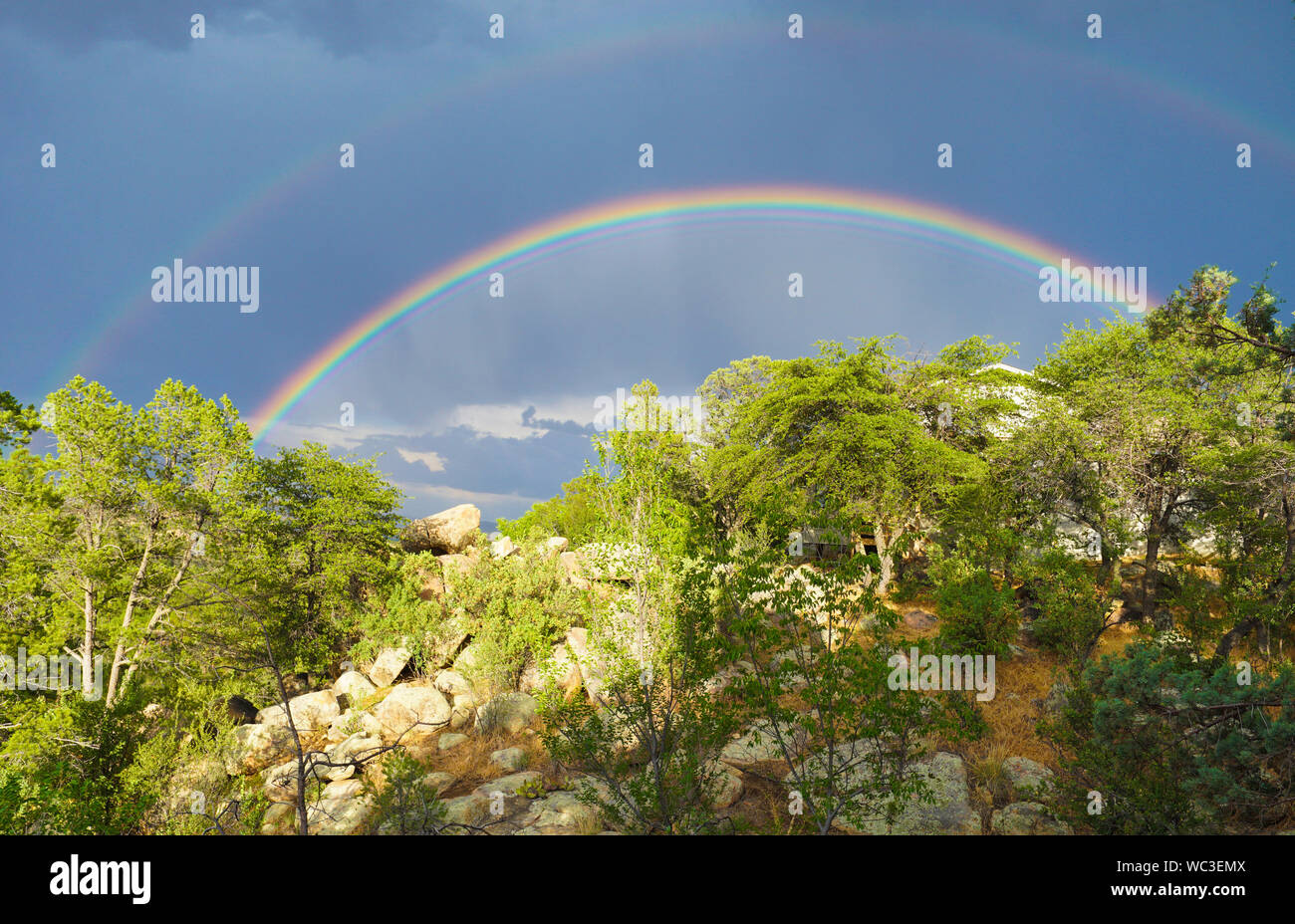 A Double rainbow shines brightly over the high desert landscape. Stock Photo