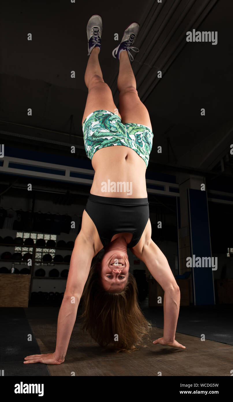 An attractive young woman with long hair and short pants is doing a handstand walk.The smiling athlete is doing a functional fitness workout in a gym. Stock Photo