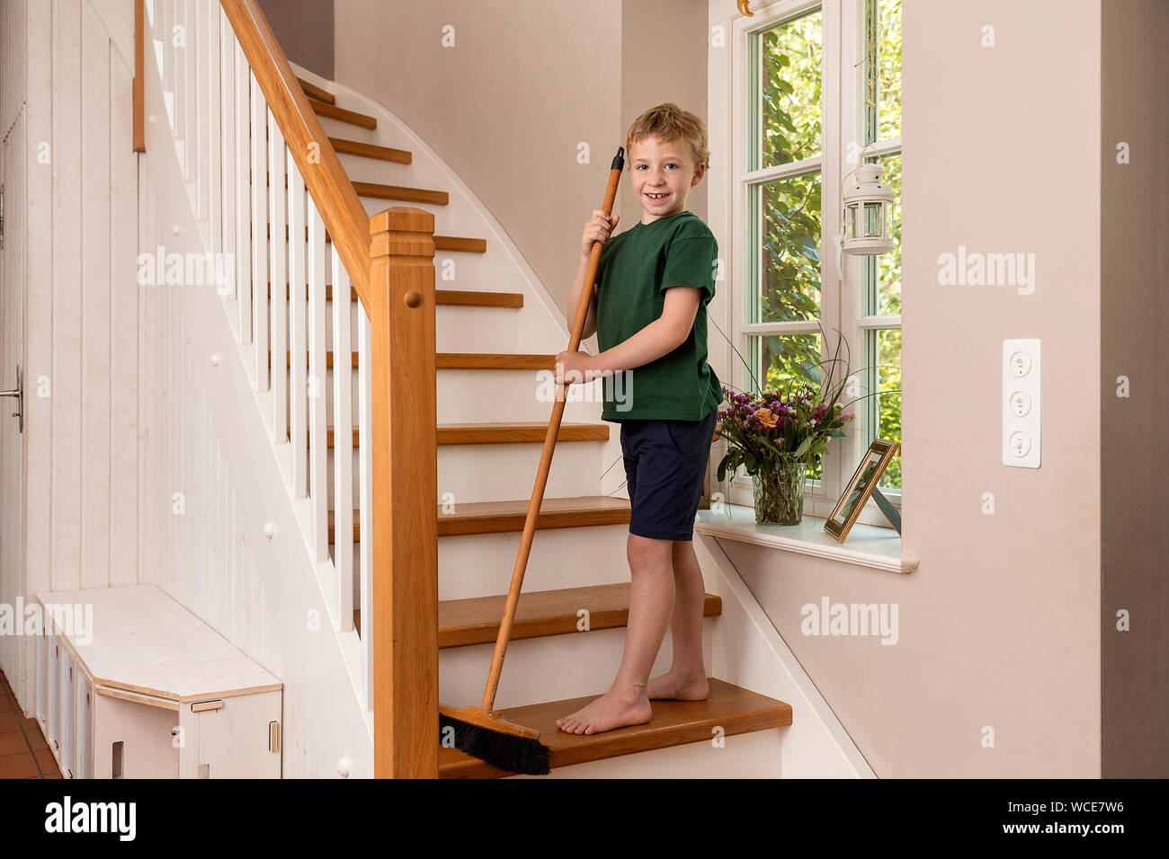Boy, 8 years, helping at home in the household, sweeping the stairs with a broom. Stock Photo