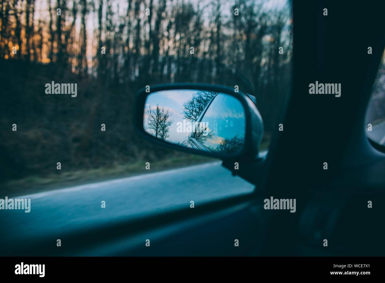 A beautiful shot of trees and the blue sky reflected on a cars side mirror with a blurred road in the background Stock Photo