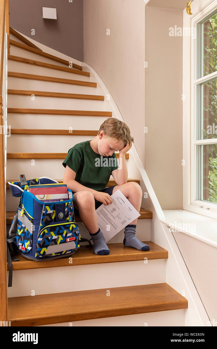 Disppointed boy, 8 years, at home with his primary school report. Stock Photo