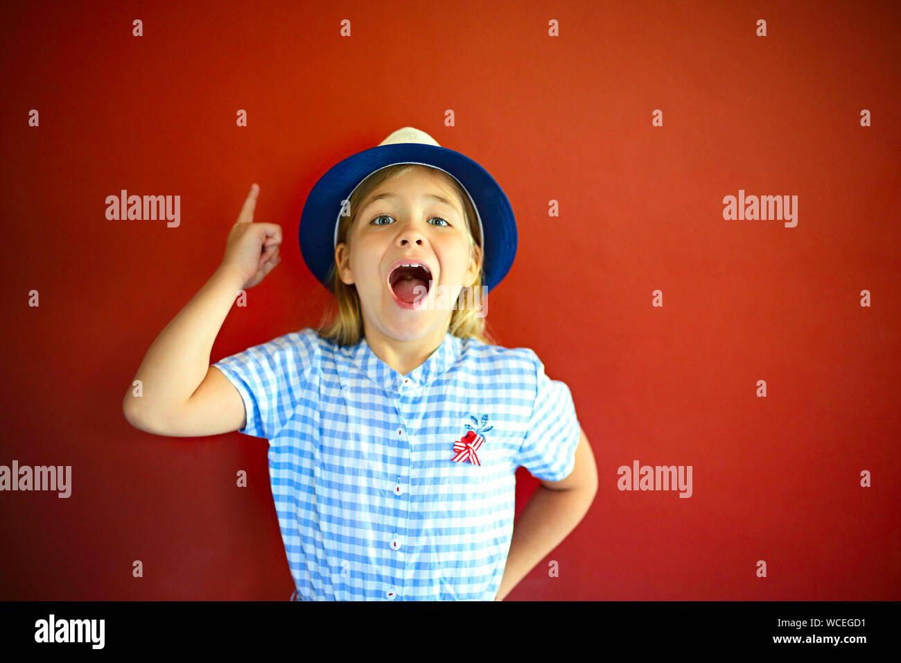 Pretty emothional children wear a hat on a red background. Copy space, daylight Stock Photo