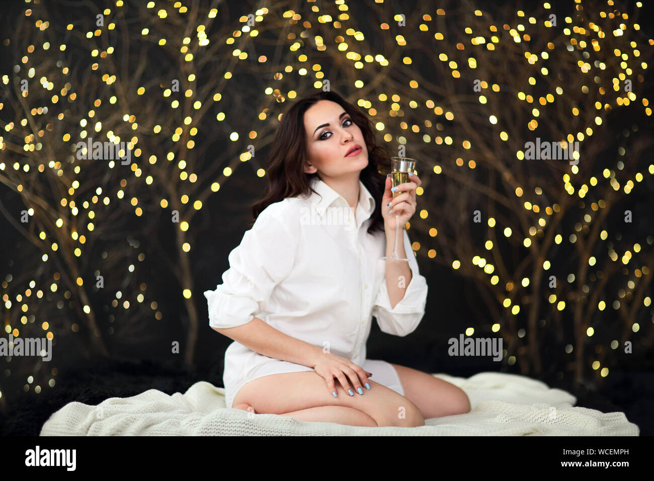 Smiling woman in white shit with glass of champagne over lights background. Party, drinks, holidays, luxury, friendship and celebration concept Stock Photo