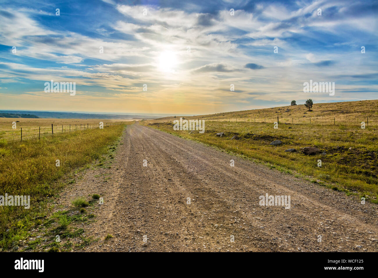Dirt Road Amidst Landscape Against Sky During Sunset At Bighorn National Forest Stock Photo