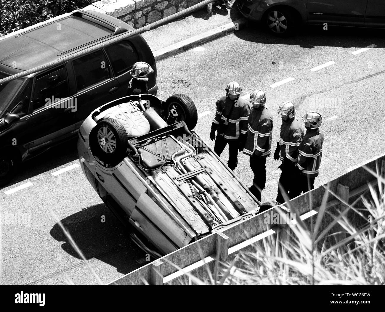High Angle View Of Rescue Workers Standing Near Overturned Car Stock Photo