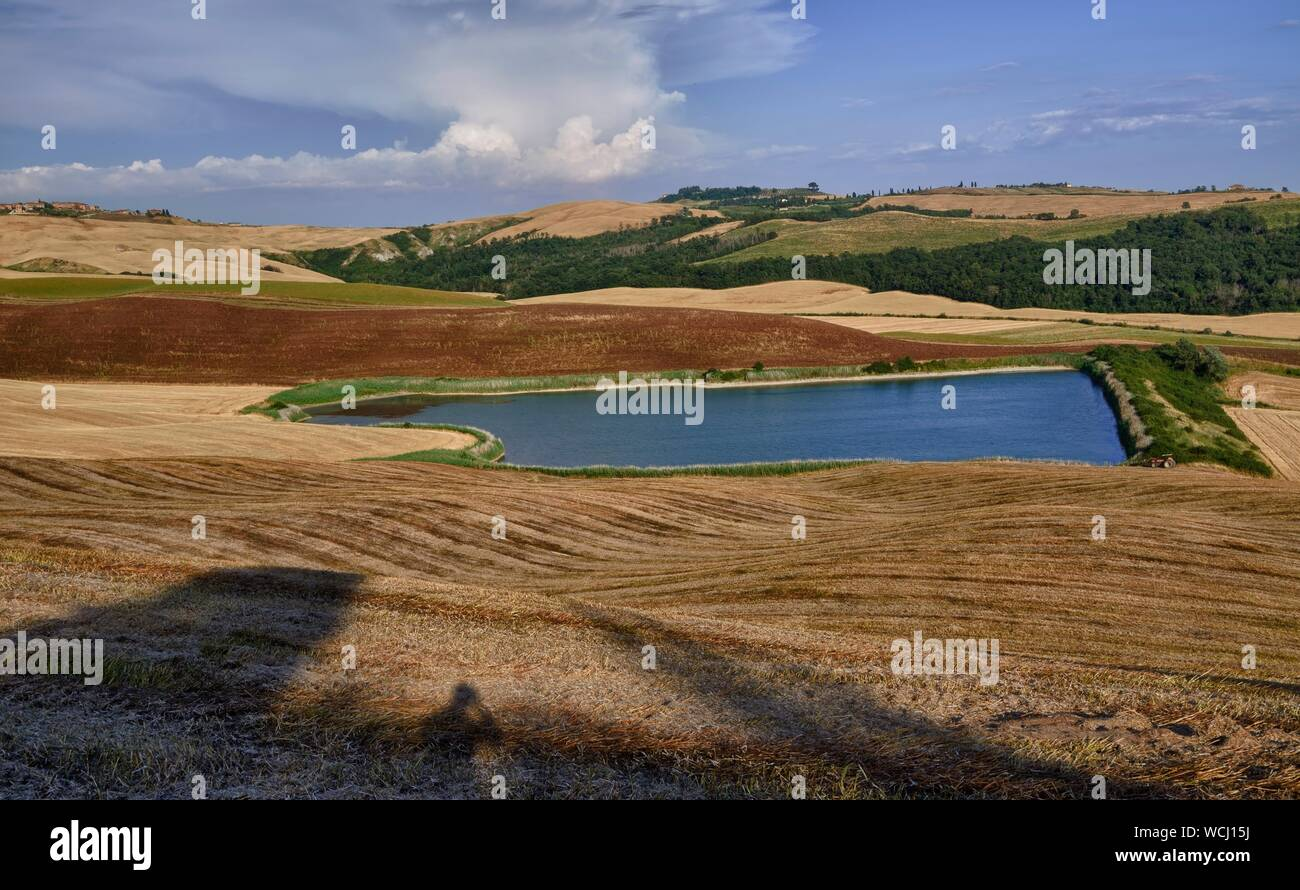 Scenic View Of Lake By Hills At Crete Senesi Against Sky Stock Photo