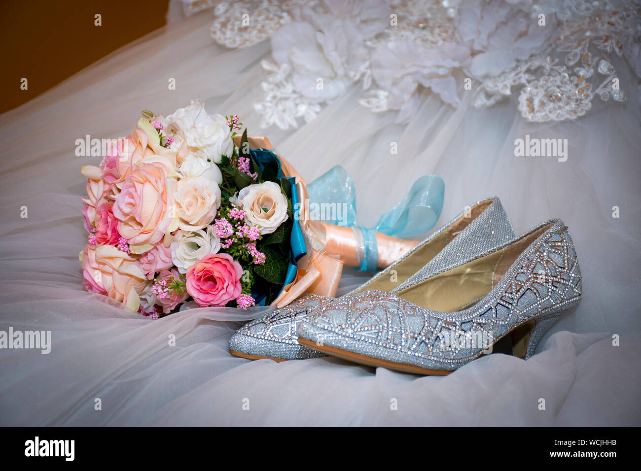 Close Up High Angle View Of Bouquet And Shoes On Wedding Dress
