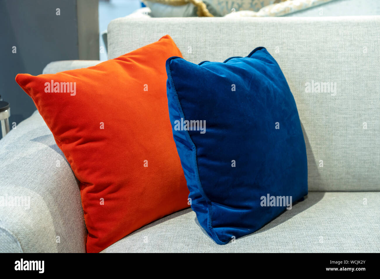 Superb Orange And Blue Decorative Pillows On A Beige Sofa Stock Machost Co Dining Chair Design Ideas Machostcouk