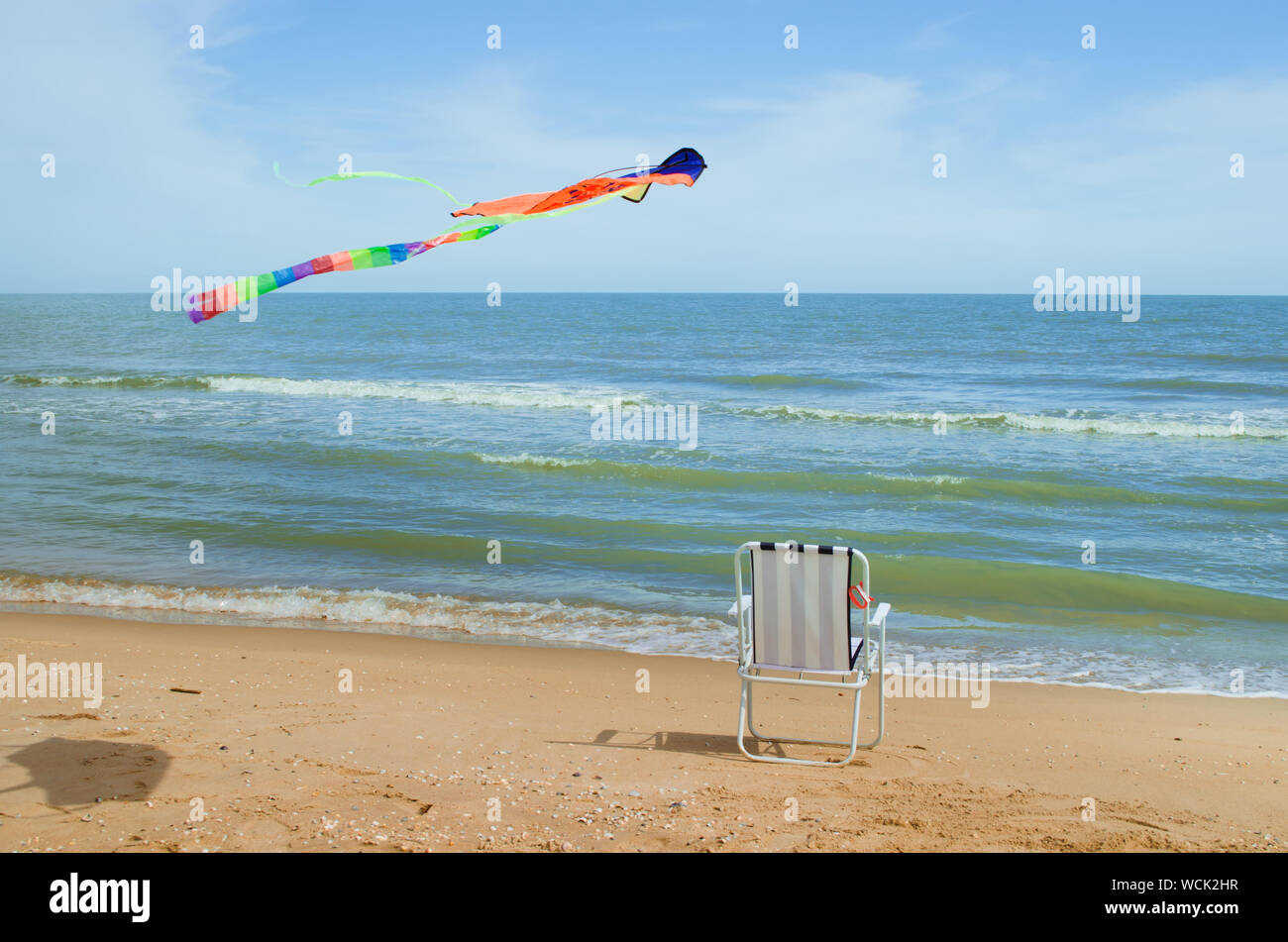 Sensational Kite Flying Over Folding Chair At Beach Stock Photo Squirreltailoven Fun Painted Chair Ideas Images Squirreltailovenorg