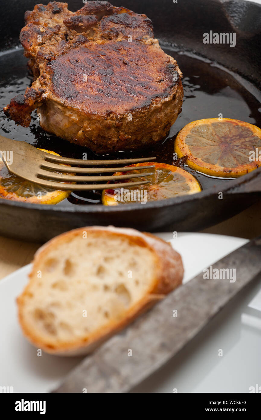 Lamb Chops And Lemons In Frying Pan On Table Stock Photo