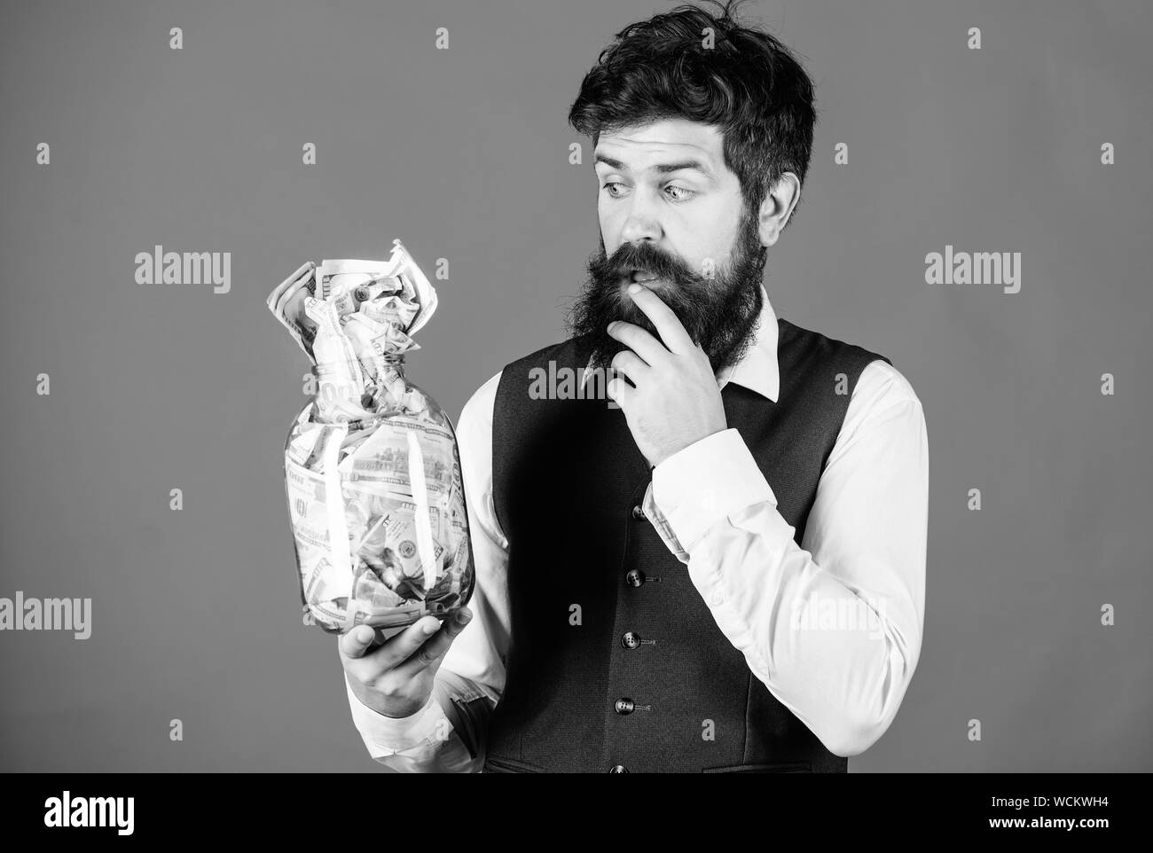 Takes money to make money in his business. Bearded man think of investing money in startup business. Businessman holding money in glass jar. Business and finance. Business savings. Stock Photo