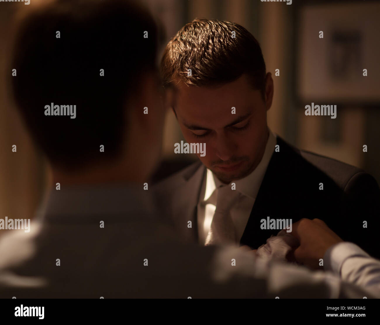 Rear View Of Groomsman Adjusting Napkin For Bridegroom Stock Photo