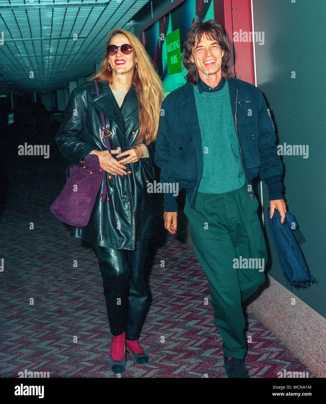 Mick Jagger and Jerry Hall arriving at London's Heathrow Airport in February 1993. Stock Photo