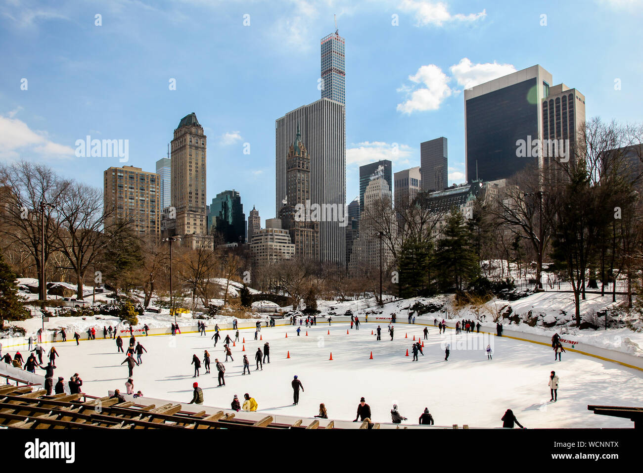 NEW YORK,NY, USA-FEBRUARY 18, 2015: Winter day scenery with New York city architecture skyline and ice rink in Central Park in New York City. Stock Photo