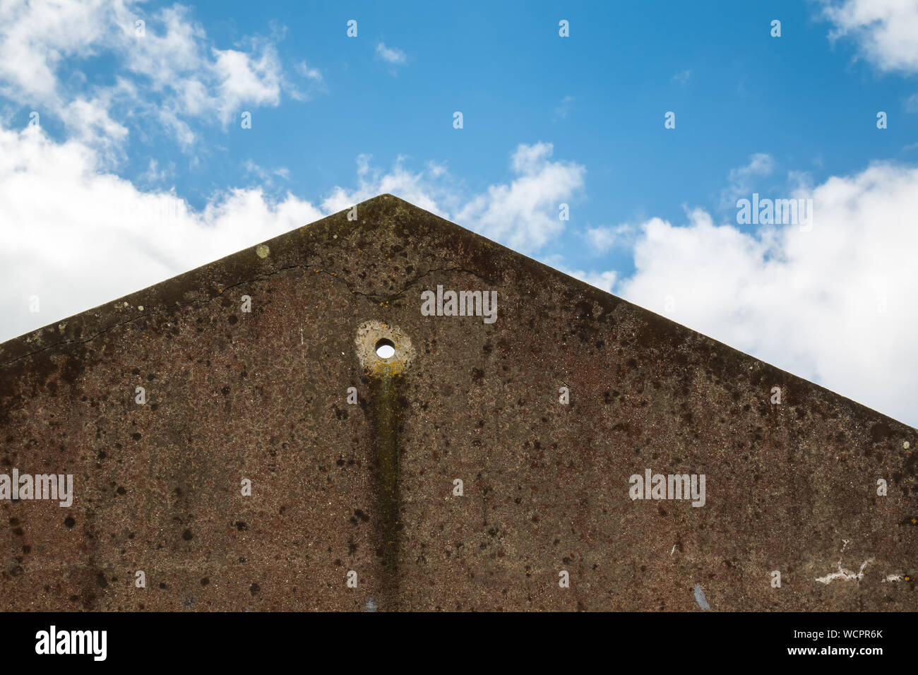Wall of an old abandoned house, creating a tringle with the roof line. Circular hole in the wall. Blue sky with white clouds. Sao Miguel, Azores Islan Stock Photo