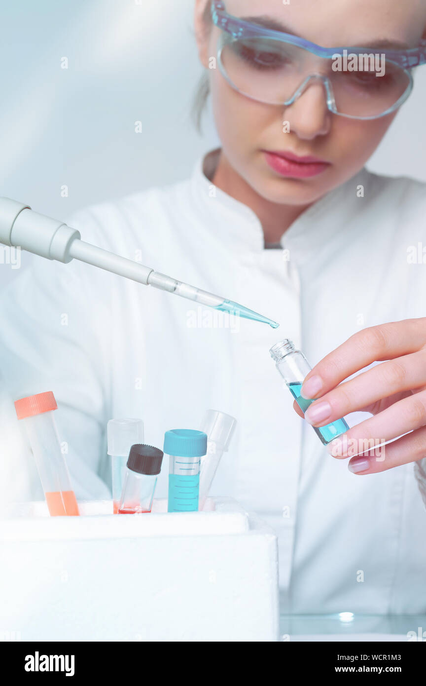Young female scientist loads liquid sample into disposable plastic vial, scientific background with copy-space, shallow DOF, focus on the vial and pip Stock Photo