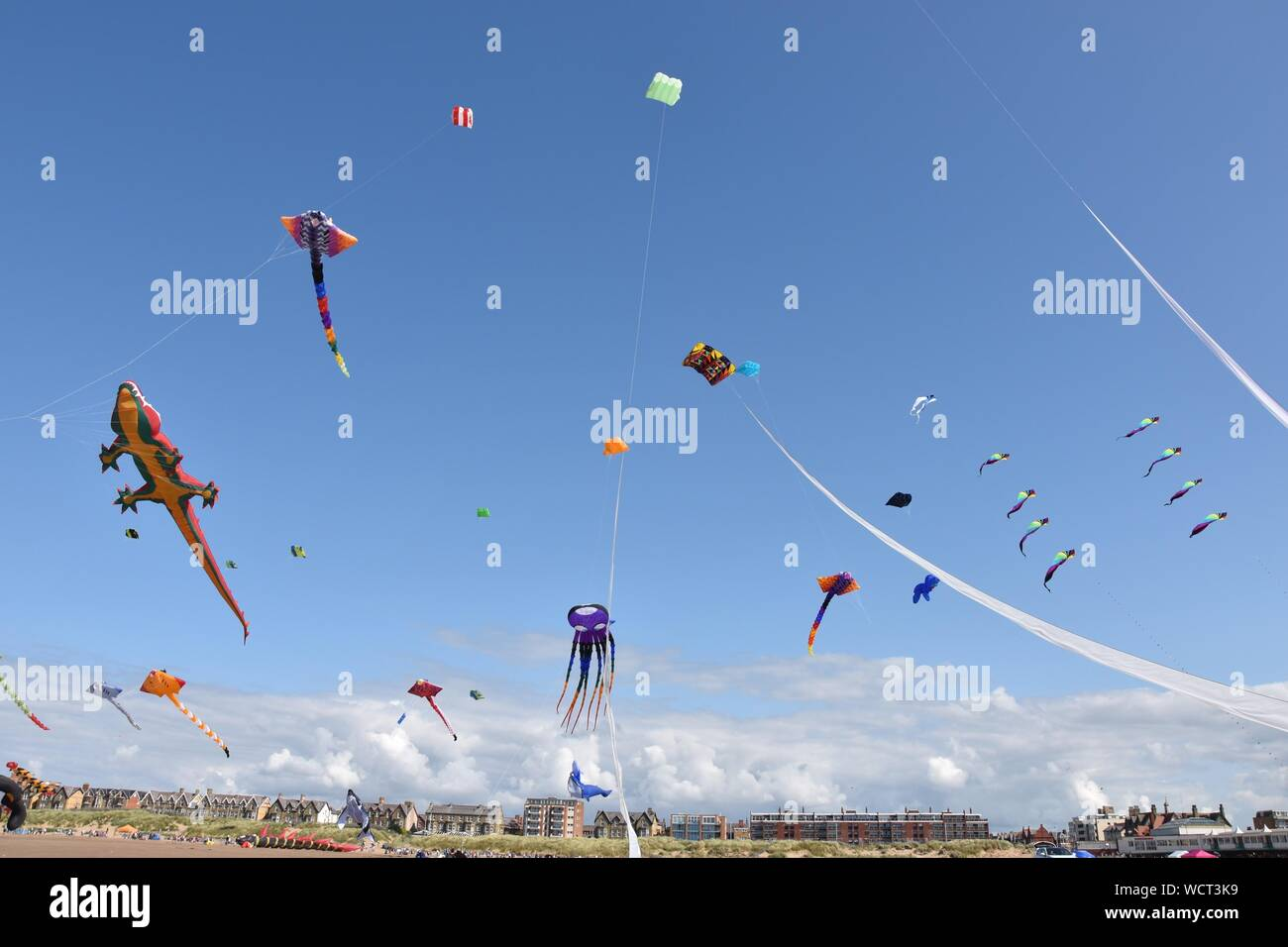 Low Angle View Of Kites Flying Against Blue Sky Stock Photo