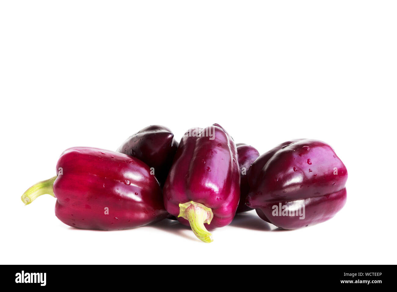 five violet peppers on a white background. Stock Photo