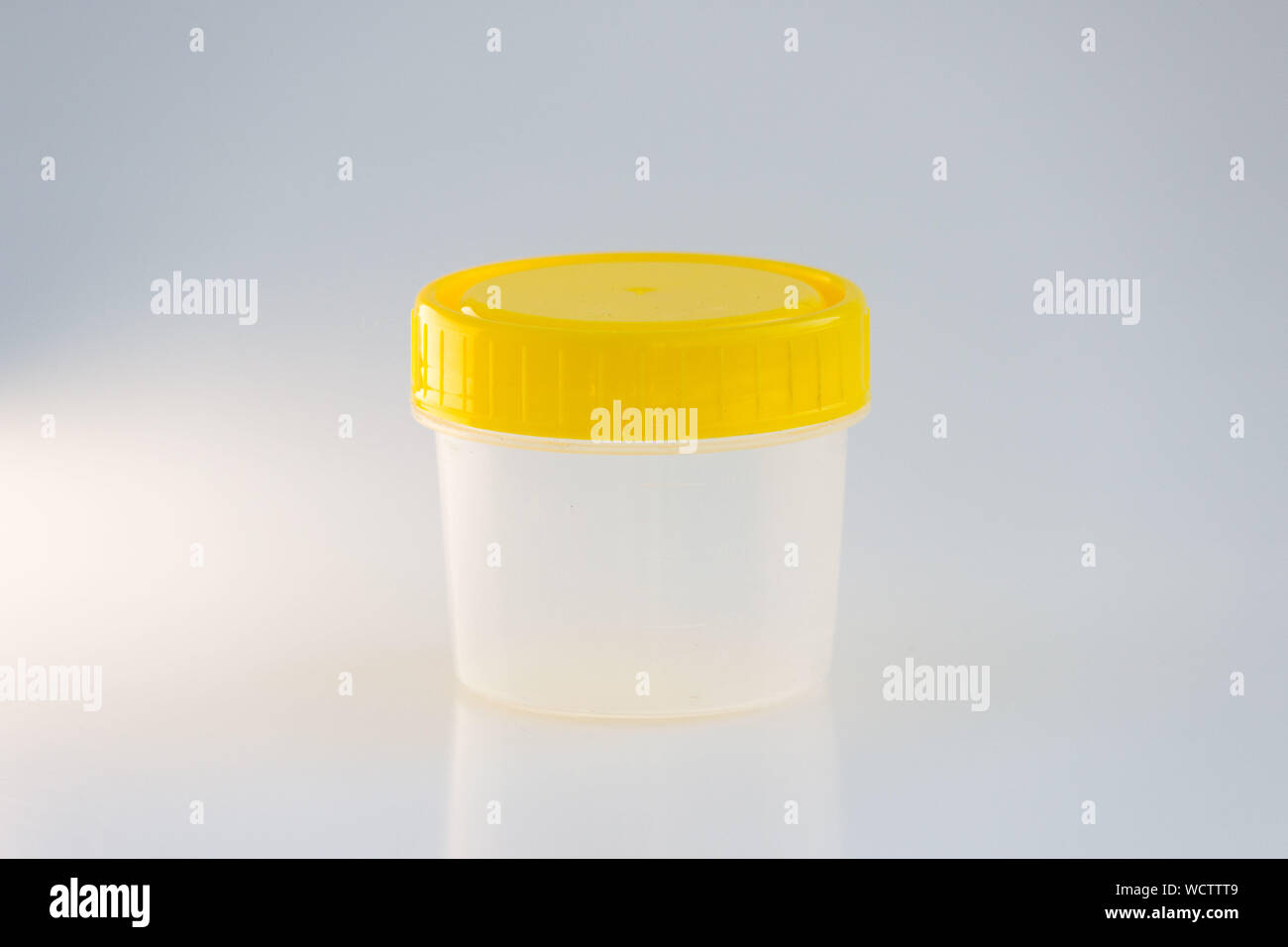 transparent plastic jar with a yellow lid on a white background. for analysis. Stock Photo