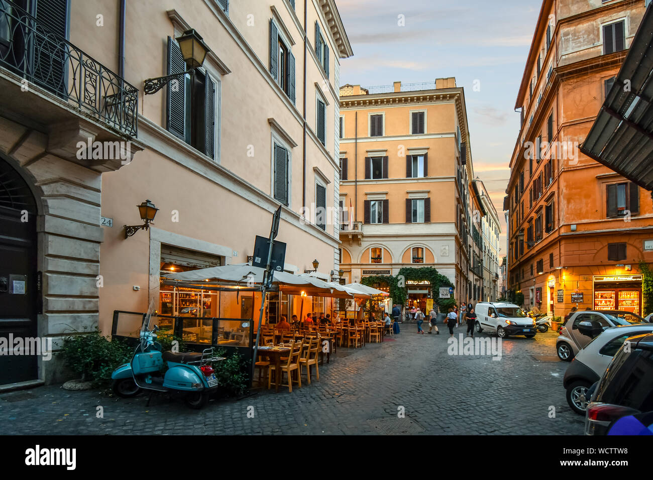 Dusk in the historic center of Rome Italy as tourists and locals enjoy early evening at the sidewalk cafes and shops. Stock Photo