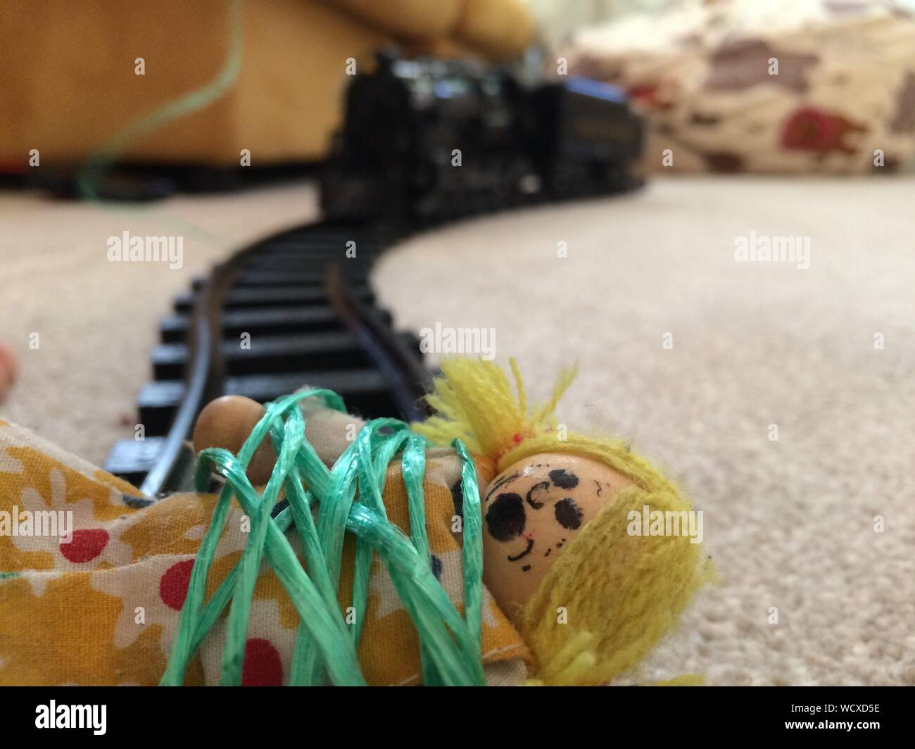 Doll Tied On Toy Train On Track At Home Stock Photo
