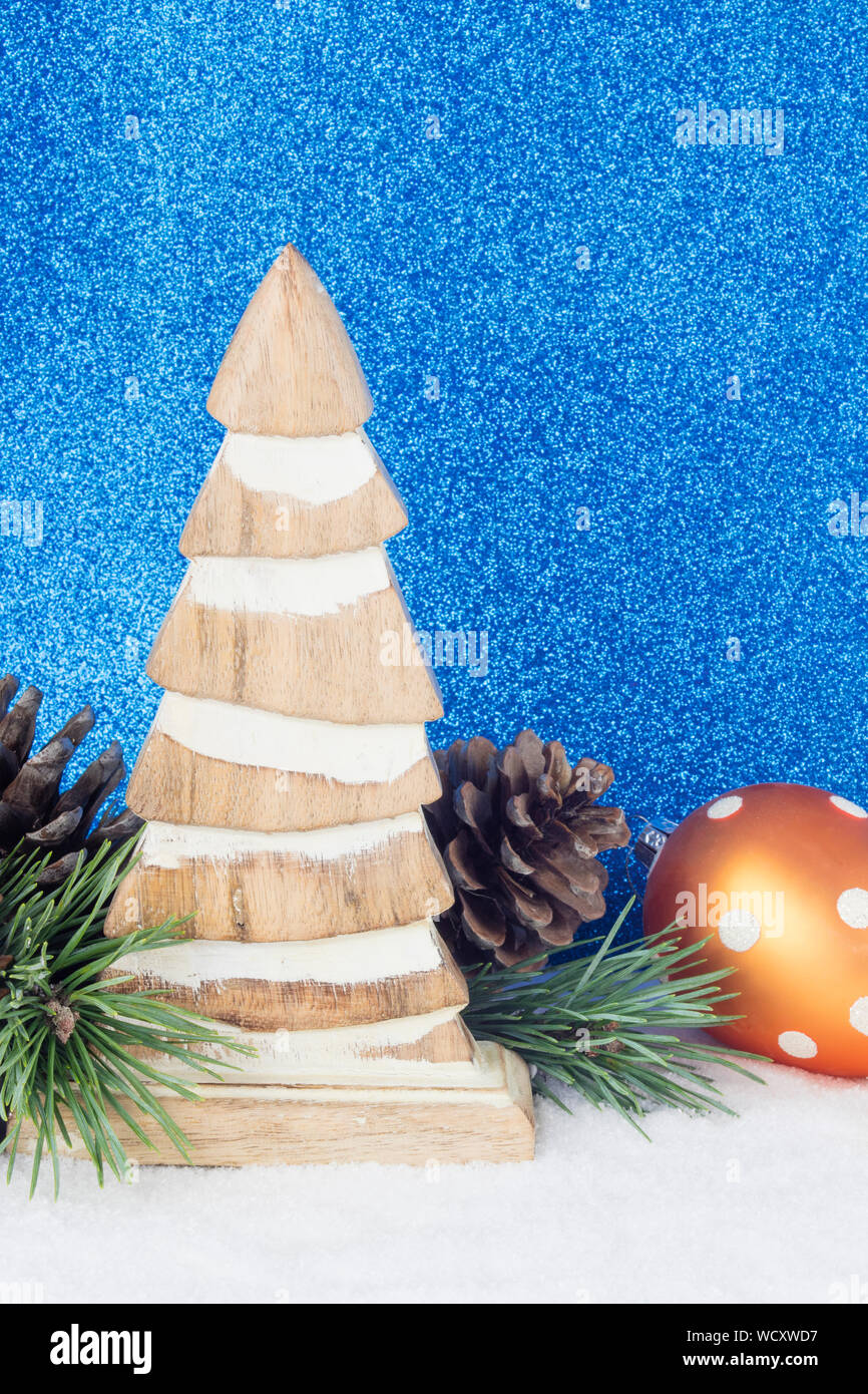 artificial christmas tree and pine cones against blue wallpaper WCXWD7