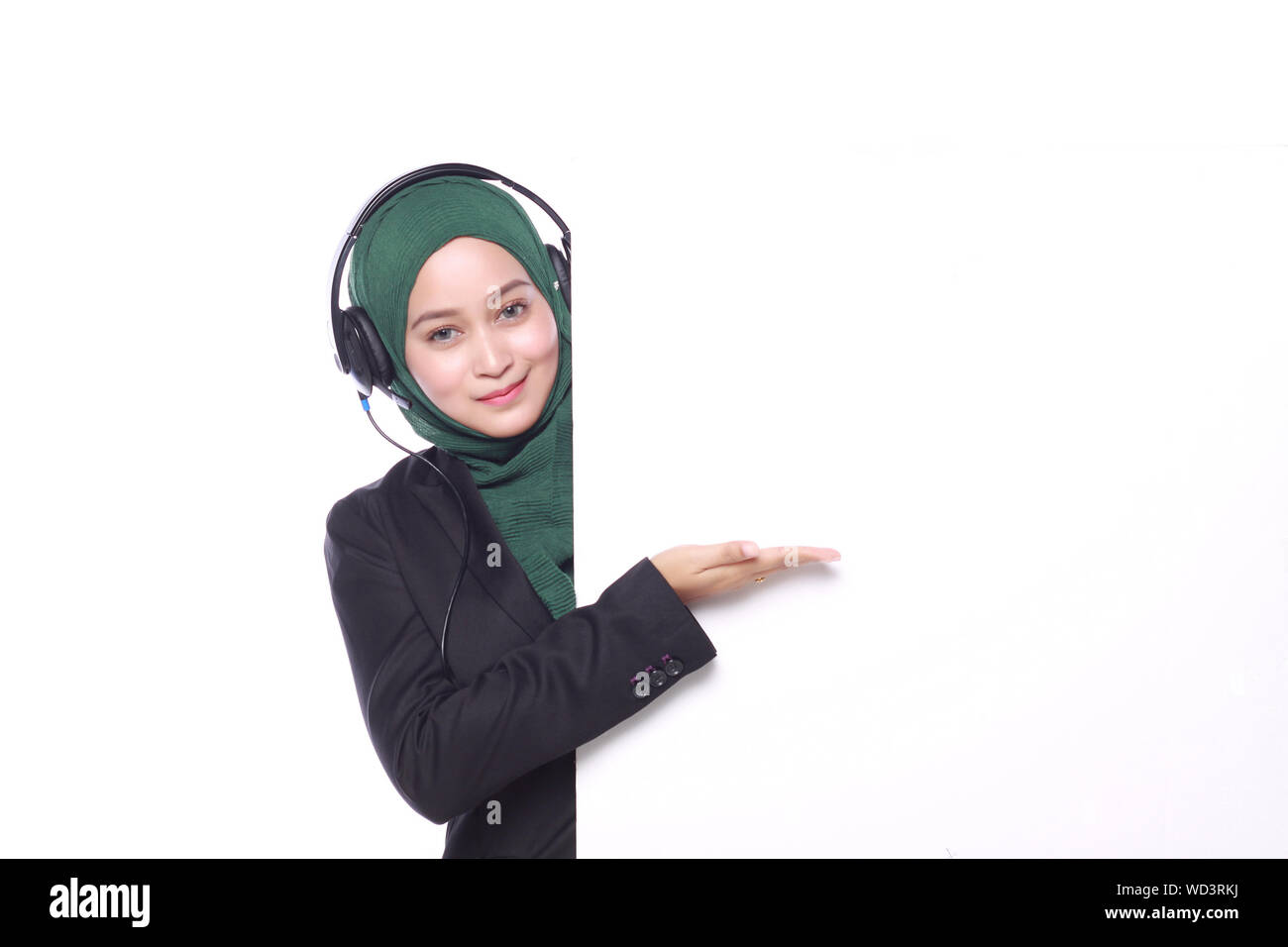 Portrait Of Confident Businesswoman With Headphones Wearing Hijab Against White Background Stock Photo