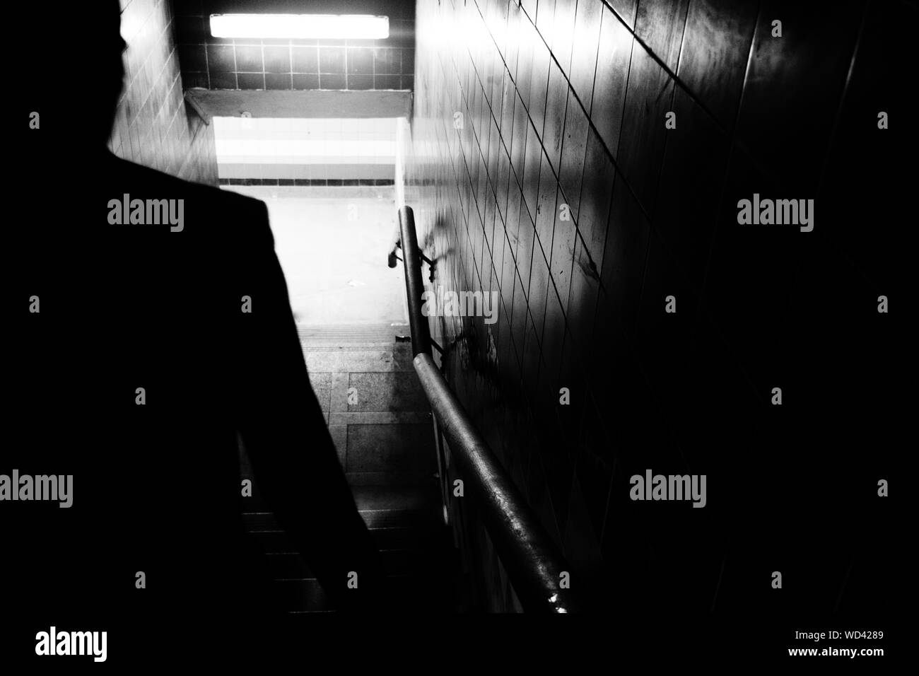 Silhouette Man Walking On Steps In Tunnel Stock Photo