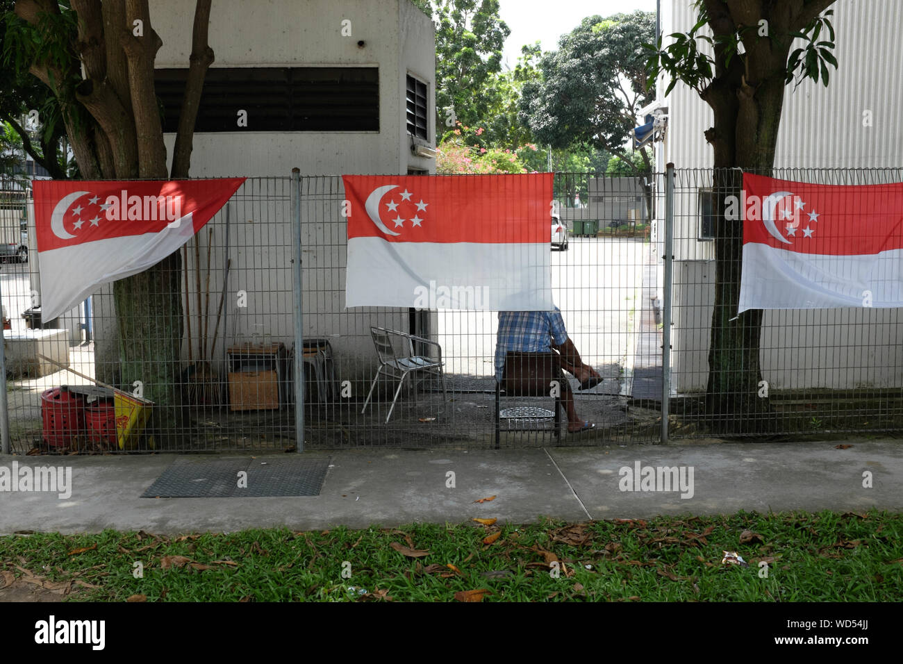 Singaporean Flags On Fence Against Building Stock Photo
