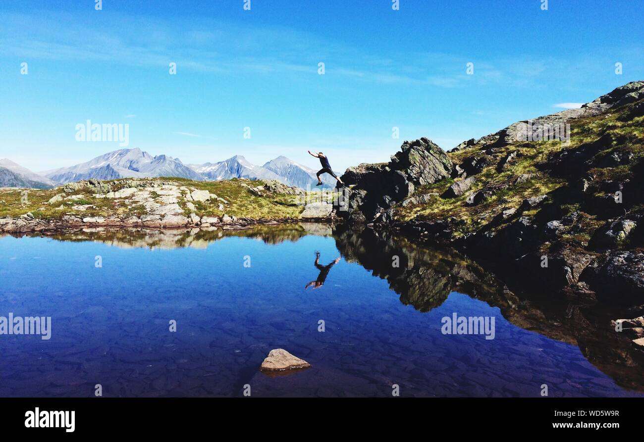 Full Length Of Man Jumping On Lake At Mountain Against Blue Sky Stock Photo
