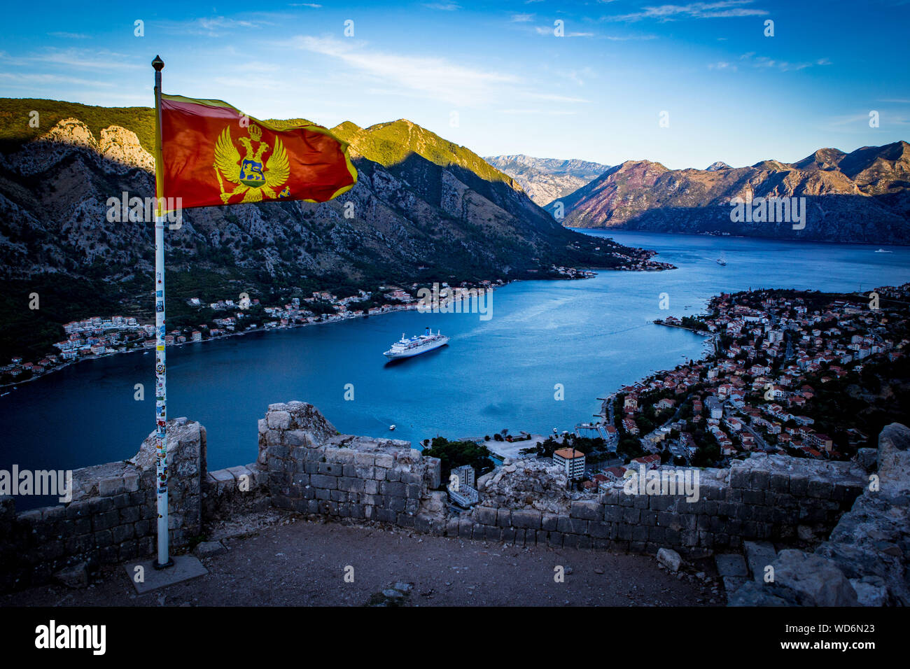 Montenegrin Flag Waving Against River And Mountains Stock Photo